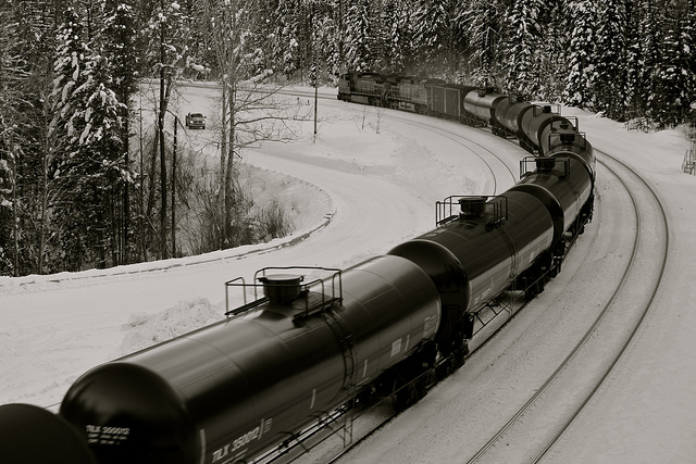 An oil-carrying train rolls through a snowy landscape