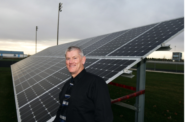 Principal Jeff Nance stands by one of four sets of solar panels at WACO High School in Wayland. This set operates lights for the school's football field. (John Gaines/The Hawk Eye)