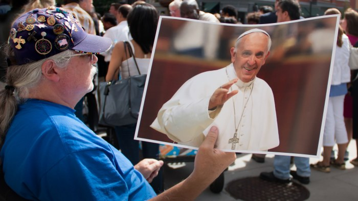 A vendor holds a Pope Francis poster outside St. Patrick's Cathedral in New York (Victoria Pickering / Flickr)