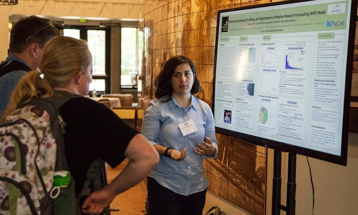 Negin Sobhani (right), a SIParCS student from Iowa State, explains her research on profiling the WRF model to attendees of the 2015 RMACC Symposium in Boulder, Colorado. (Brian Bevirt / CISL)