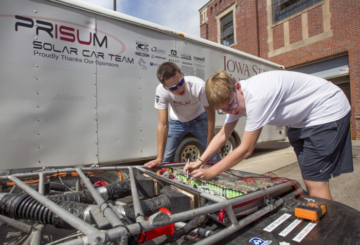 PrISUm team members Charlotte Brandenburg, right, and Matt Goode look over the car's batteries and fuses outside the team's Sweeney Hall garage. (Christopher Gannon/Iowa State University News Service)